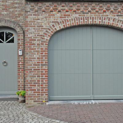 Pastorie sectionaalpoort in aluminium panelen en een aluminium voordeur met beglazing