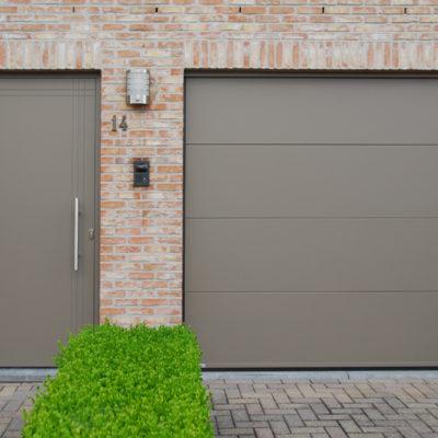 Sectionaalpoort met vlakke BUMAX panelen en aluminium voordeur met vertikale en horizontale infrezingen