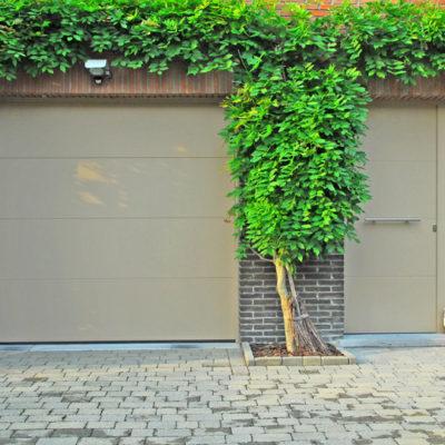 Sectionaalpoort in aluminium met vlakke BUMAX panelen en Pre?sence voordeur met horizontale infrezingen
