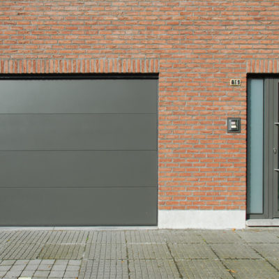 Sectionaalpoort met vlakke aluminium panelen en aluminium voordeur met zijlicht en gezandstraald glas