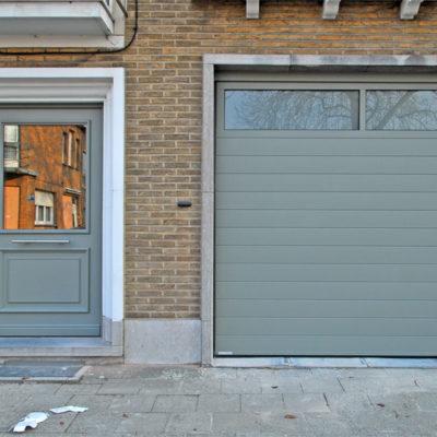 Sectionaalpoort met gelijnde BUMAX panelen, glassectie bovenin en een aluminium Pre?sence voordeur in Tradition stijl en drievoudige beglazing in de bovenste moulure