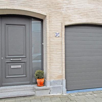 Sectionaalpoort in gelijnde BUMAX panelen en Pre?sence Tradition voordeur met ingewerkte moulures en 2 zijlichten