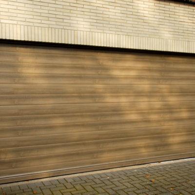 Sectionaalpoort in gelijnde BUMAX profielen met Renolit folie in vergrijsde Cederhout kleur