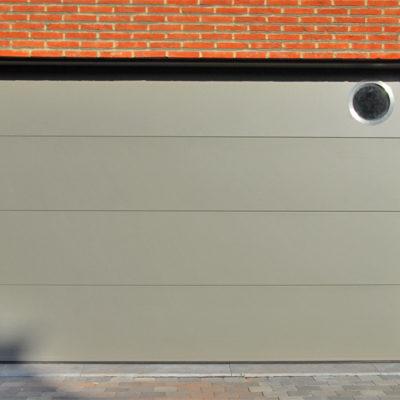 Sectionaalpoort met vlakke BUMAX panelen en een rond inox raam bovenin