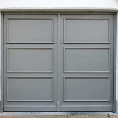 Sectionaalpoort in aluminium kaders met houten Bruynzeel platen en opgewerkte moulures met sierplint onderaan en vertikale makelaar in het midden