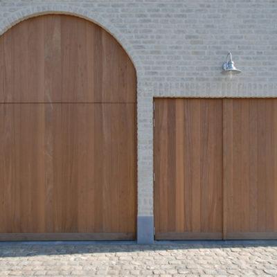 Kantelpoort en buitendraaiende vleugelpoort in aluminium kaders en houten bekleding in Louro Gamela