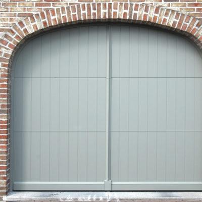 Sectionaalpoort in 3 aluminium panelen, voorzien van sierplint onderaan, vertikale makelaar in het midden en een sierboog rond de poort