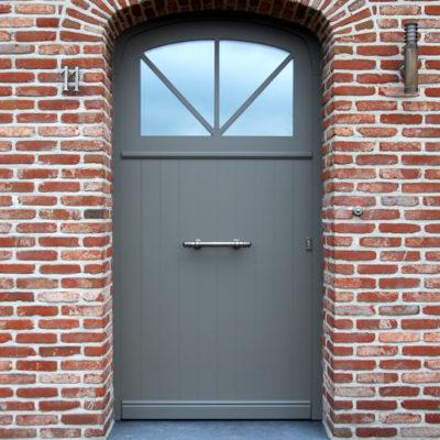 Pastorie voordeur voorzien van een gebogen raam met sierlijst eronder en een valse center rondom de deur
