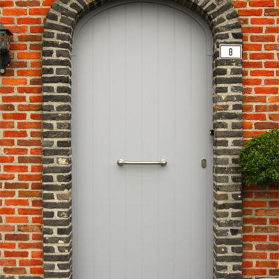 Pastorie voordeur met sierplint onderaan en een valse center