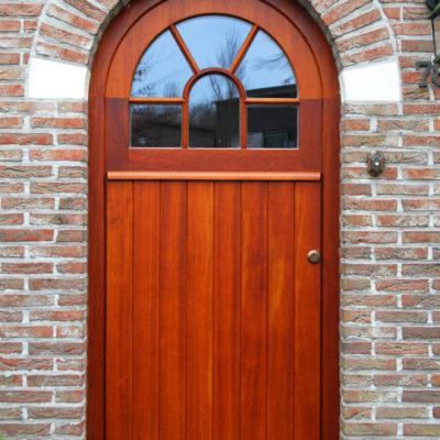 Voordeur in Afzelia hout met gebogen raam bovenaan en vertikale planchetten