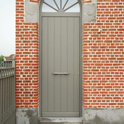 Pastorie voordeur met Bruynzeel plaat gelakt in een Ral-kleur en gebogen bovenlicht met kruisverdeling