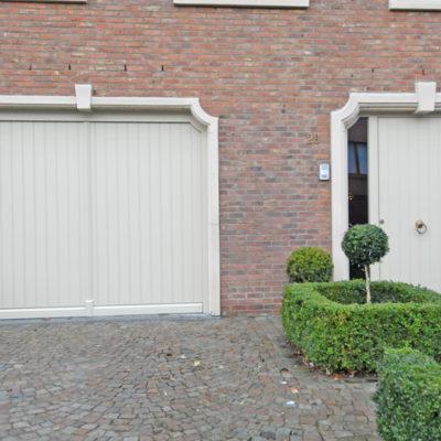 Pastorie kantelpoort in aluminium kaders en houten bekleding en houten voordeur met 2 zijlichten