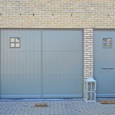 Pastorie sectionaalpoort in aluminium kaders met aluminium opdekpanelen en Presence pastorie voordeur met vierkant raam