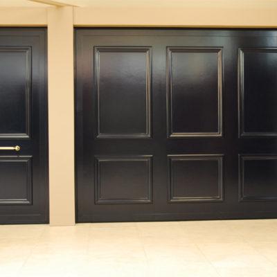 Aluminium kantelpoort met oplegmoulures en bijhorende voordeur