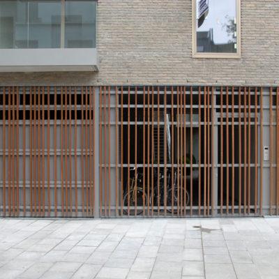 Gevelbekleding met sectionaalpoort en deuren bekleed met vertikale houten IPE balken