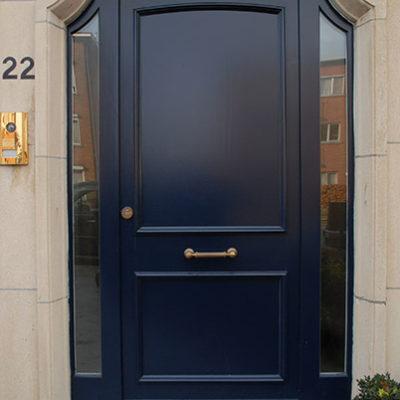 Houten voordeur met oplegmoulures en 2 zijlichten