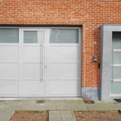 Kantelpoort in aluminium met ingewerkte loopdeur en bijhorende voordeur