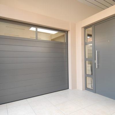 Sectionaalpoort in Bumax panelen met glassectie en Presence voordeur type Uni 6