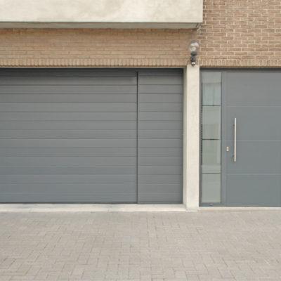 Sectionaalpoort in fijn gelijnde Bumax panelen met vast zijpaneel en zijraam en Presence voordeur type Uni 3 met zijlichten