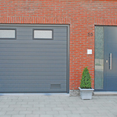 Sectionaalpoort in fijn gelijnde staalplaat panelen met 2 ramen en Presence voordeur type Uni 6 met zijlicht