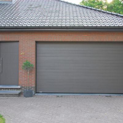 Sectionaalpoort in gelijnde Bumax panelen en Presence voordeur type Uni 3 met zijlicht