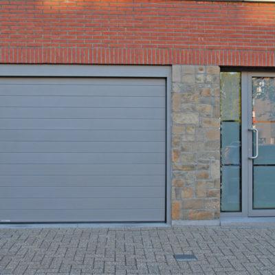 Sectionaalpoort in gelijnde Bumax panelen en voordeur voorzien van gezandstraald glas met klare boorden en lijnen