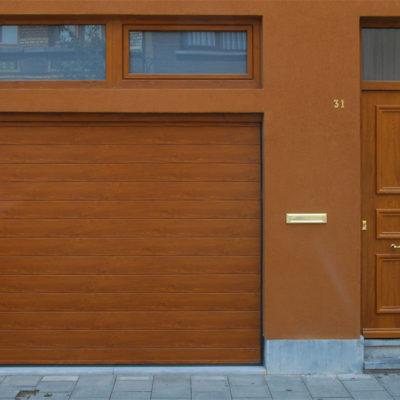 Sectionaalpoort in gelijnde Bumax panelen in houtimitatie folie en Presence voordeur type Charente