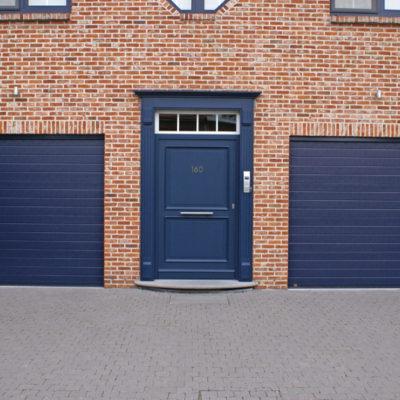 Sectionaalpoorten in fijn gelijnde staalplaat panelen en houten voordeur