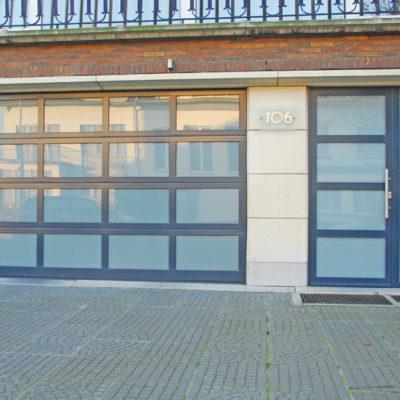Sectionaalpoort in aluminium glaspanelen met opaal gelaagd glas en bijhorende voordeur