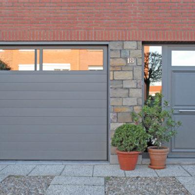 Sectionaalpoort in fijn gelijnde Bumax panelen met glassektie en aluminium voordeur