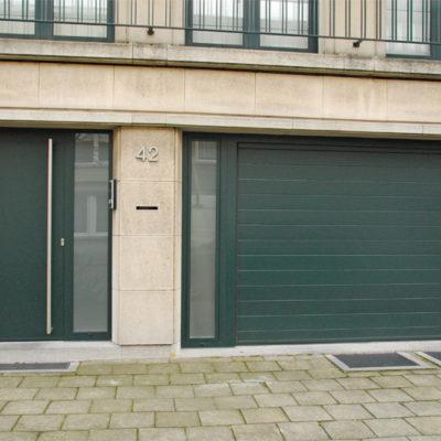 Sectionaalpoort in fijn gelijnde Bumax panelen met vast zijraam en Presence voordeur met vlak paneel