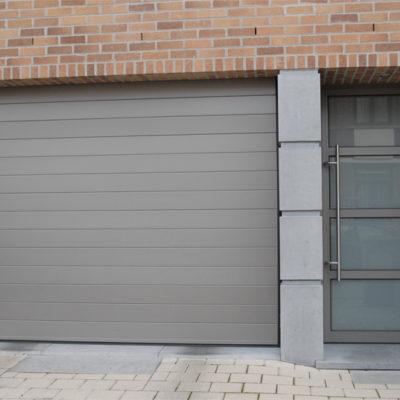 Sectionaalpoort in gelijnde Bumax panelen en voordeur met 3 T profielen