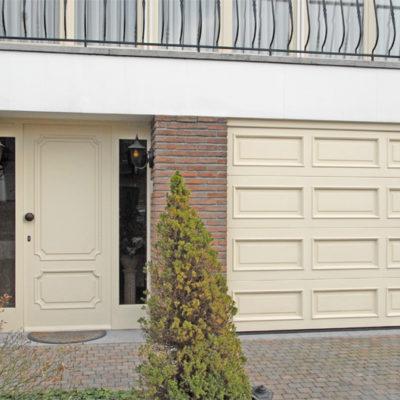 Sectionaalpoort in houten panelen met oplegmoulures en voordeur met zijlichten