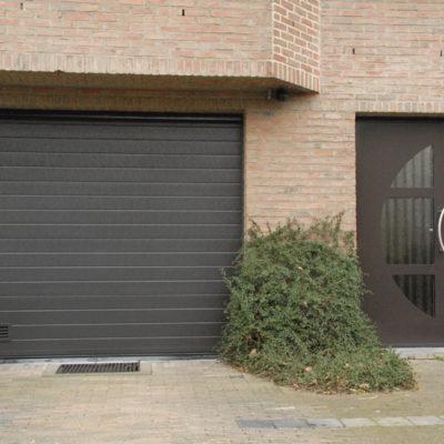 Sectionaalpoort in vlakke staalplaat panelen en Presence voordeur type Eclips met zijlicht