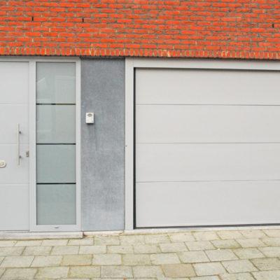 Sectionaalpoort in vlakke staalplaat panelen en Presence voordeur type Uni 3 met zijlicht