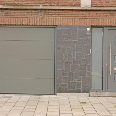 Sectionaalpoort in vlakke staalplaat panelen en aluminium voordeur met sierpaneel type Tristar