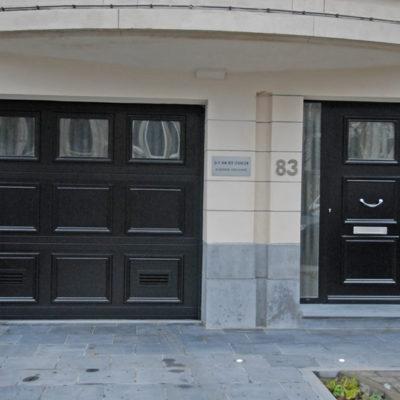 Sectionaalpoort in aluminium kaders en bekleding met sandwichpanelen met oplegmoulures en Presence voordeur type Bretagne met glas bovenin en 2 zijlichten