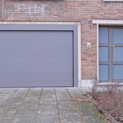 Sectionaalpoort met fijn gelijnde staalplaat panelen en volledig verglaasde voordeur met 2 T profielen