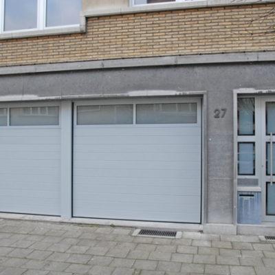 Sectionaalpoorten in gelijnde Bumax panelen met glassektie bovenin en verglaasde voordeur
