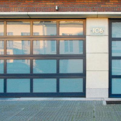 Verglaasde voordeur met bijhorende sectionaalpoort in glassecties
