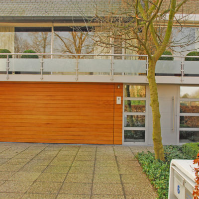Volledige gevelbekleding met kantelpoort in aluminium kaders met cederhouten planken en Presence voordeur type Uni 6